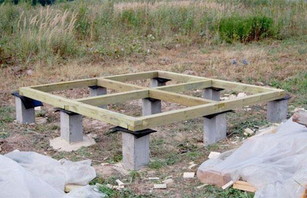 Основной опорой для дровяника служат столбы фундамента