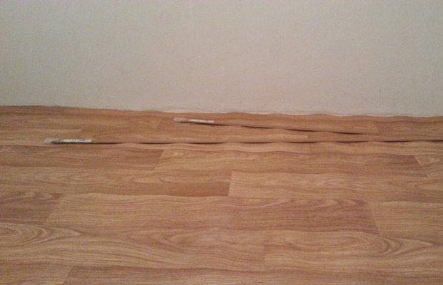 Прежде, чем приступить к выравниванию линолеума при помощи утюга, между стеной и полотном нужно вырезать небольшую щель