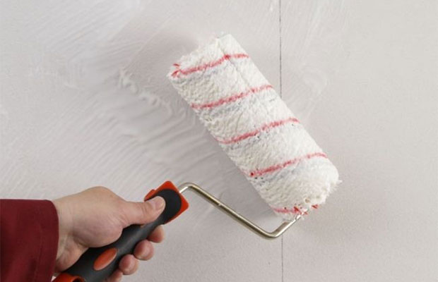 Клеящий состав наносится на поверхность стены валиком или шпателем