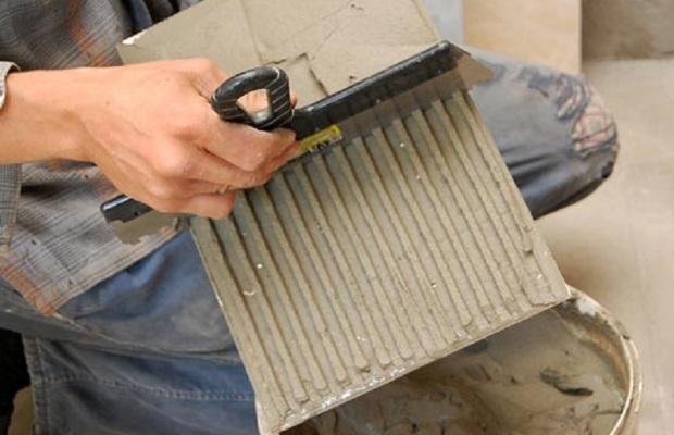 Для укладки плитки используется широкий шпатель с квадратными зубцами