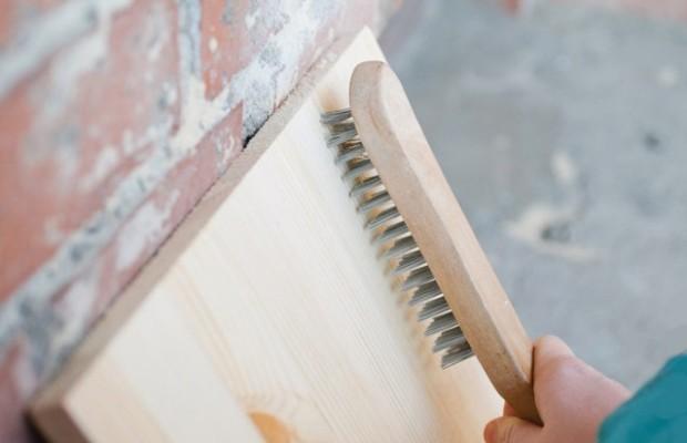 Использование жесткой металлической щетки с ручкой является наиболее простым способом состаривания древесины